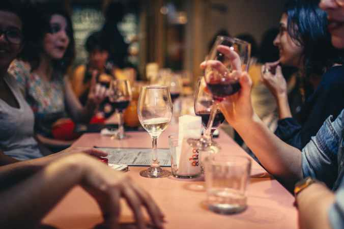 people drinking wine and talking on dining table